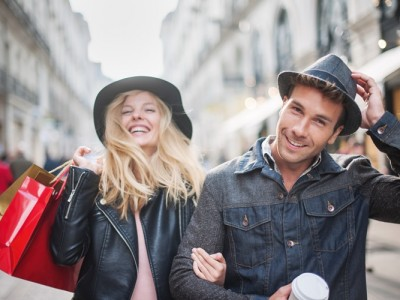 a trendy young couple  wearing hats walking in the city in autumn, the young woman wears a leather jacket , shopping bags at her arm and the man a cup of coffee in hand