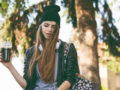 Modern teenage hipster girl in autumn in park in beanie hat, with takeaway coffee and headphones